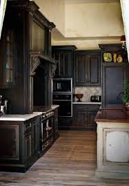 distressed black kitchen cabinets with white countertop and silver