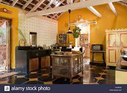 freestanding unit on black and yellow tiled floor of goan kitchen