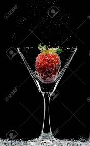 martini strawberry view of martini glass with strawberry on black background stock