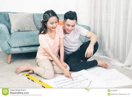 attractive young asian couple looking at house plans stock