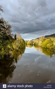 autumnal colored trees reflecting in the waters of a small river
