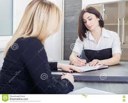 two women sitting at a table in the office blonde and brunette on