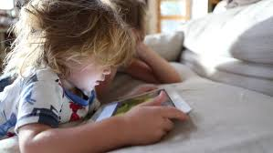 Cute Little Girl Lying On Sofa Reading Book And Smiling Stock - Lying sofa 2