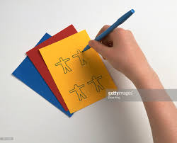 Stick Paper Child Using Blue Felt Tip Pen To Draw Stick Figures On Yellow
