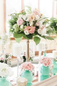 pink floral centrepiece with aqua votives and mirrored