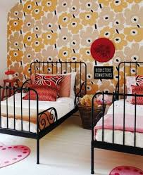 twin bedroom with half floral wallpaper and black metal bed frames