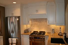 white kitchen with basket weave tile backsplash and granite