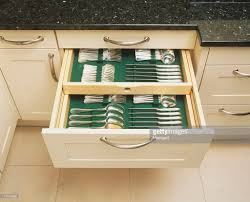 set of silver cutlery neatly stored in kitchen cabinet drawer