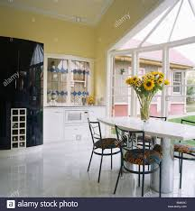 white ceramic floor tiles in modern pale yellow kitchen with