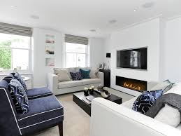 recessed lighting over fireplace velvet chairs patterned cushions black white living room recessed