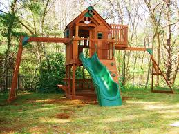 interesting backyard design with playsets and green grass plus