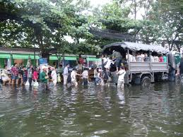 people boarding a thai military truck to escape the flooded area