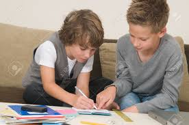 two friends doing their homework in the livingroom stock photo