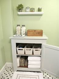 white wooden towel cabinet over toilet in gray painted bathroom