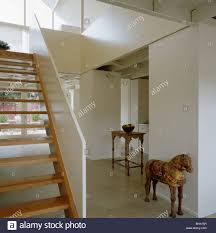 open tread wooden staircase in modern architectural white hall