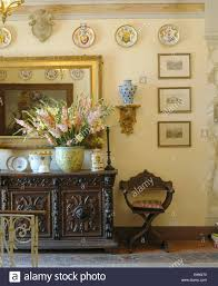 tuscany dining room large vase of gladioli on ornately carved wooden sideboard in