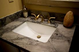 granite bathroom countertop with rectangle sink and gold colored faucets