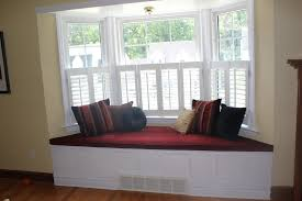 futuristic bay window design with brown curtain and floral bench