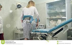 sedia ginecologica ginecologo chiede al paziente femminile di sedersi sulla sedia