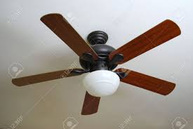 a modern ceiling fan installed on a textured white ceiling stock
