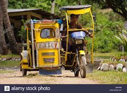 tricycle philippines asian man filipino riding a yellow tricycle motorbike with