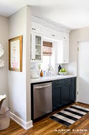 white upper cabinets and navy lower cabinets with black and white