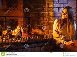happy woman relaxing at fireplace winter home stock photo