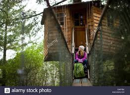woman with her backpack hanging out in front of a tree house