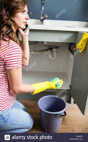 Cleaning Kitchen Sink by Woman Using Mobile Phone While Cleaning Kitchen Sink Stock Photo