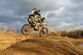 motocross biking motocross rider on his dirt bike during daytime free stock photo