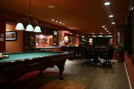 half of the game room pool table with a bar near it a place
