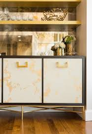 black and gold buffet cabinet with mirrored backsplash