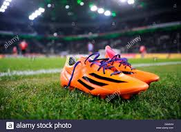 buy football boots germany orange coloured adidas football boots on the edge of the pitch
