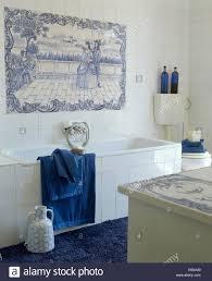 coastal bathroom with blue white tiled mural on wall above bath