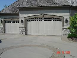 two car garage with white door and brick wall of exterior