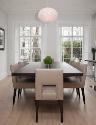 a formal dining room with bay window ladder back chairs