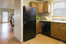 Kitchen Refrigerator Cabinet View Of A Kitchen With A Black Refrigerator And Wood Cabinets
