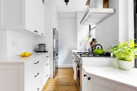 white kitchen cabinets with black hardware white walls and black hardware in a windowed pre war kitchen