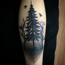 black ink pine tree tattoo on back leg