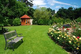 beautiful garden with blooming roses brick path bench and a