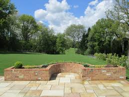 garden with curved reclaimed brick planters indian sandstone