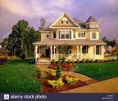large two story yellow victorian house with blue shutters and a