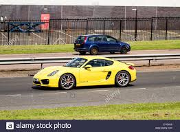 porsche yellow a yellow porsche 2 seat coupé cayman s sports car travelling along