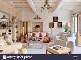stone floored provencal sitting room with armchairs floral sofa