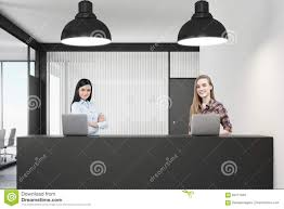 Standing Reception Desk by Two Women Standing At A Reception Desk In Office Stock Photo