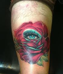 eye in rose tattoo on right thigh