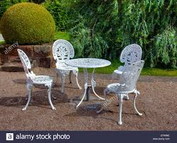 wrought iron table and six chairs in an english garden stock photo