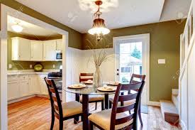 olive and white dining room with glass table and wood chairs