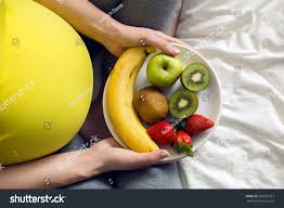bowl of fruits pregnant holding bowl fruit sitting stock photo 583591327