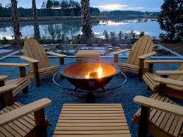 outdoor modern backyard fire pit near lake with wooden chairs